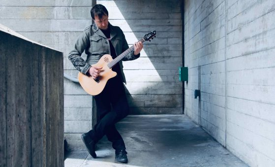 Andi Lee (the ashen) stands in a concrete stairwell, he is holding a guitar and looking down at it. He is wearing a green jacket and black jeans