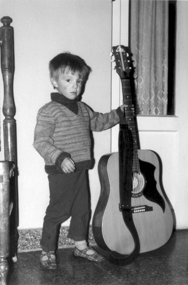 Andi with his father's guitar, aged 4